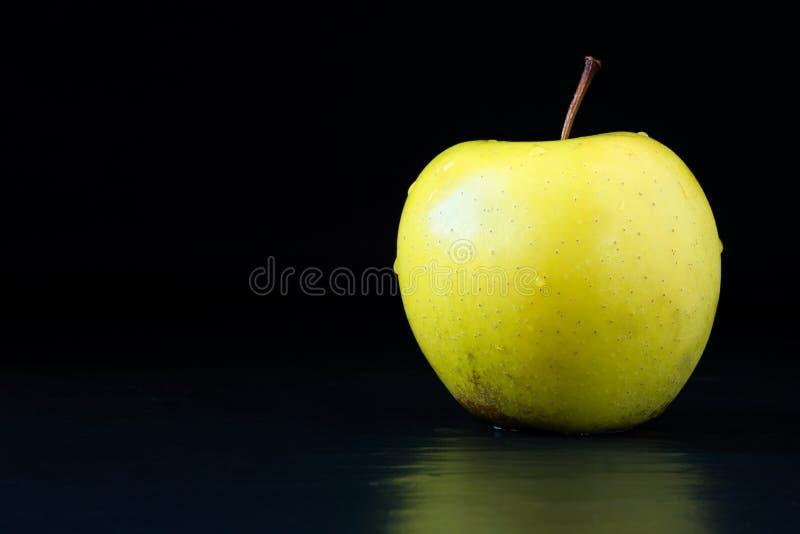 Естественный, органический, свежо помыл золотое - очень вкусное яблоко со стержнем на черной каменной поверхности с отражением и  стоковые изображения rf