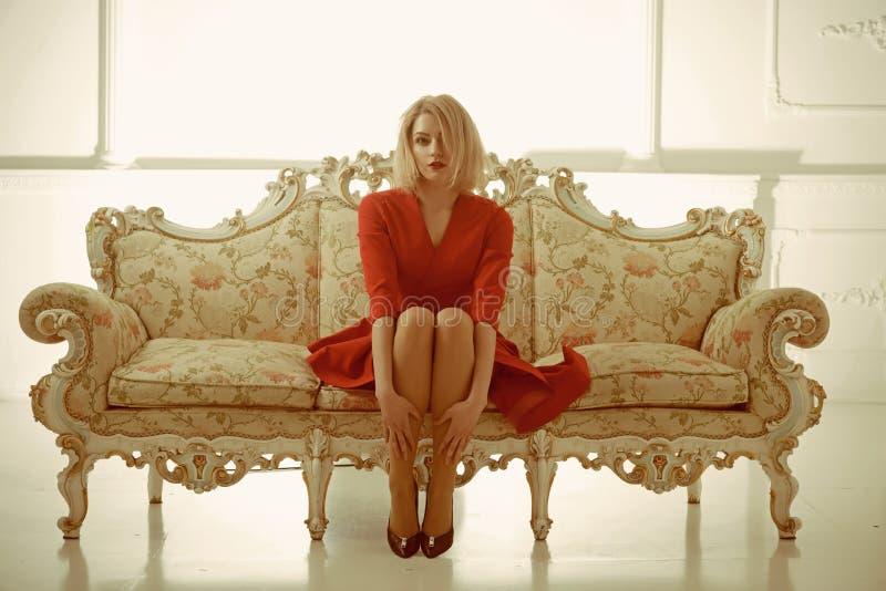 Желанные гости женщины хозяйки искать работы хозяйки хозяйка приема гостиницы сидит на софе в красном платье хозяюшка стоковое фото