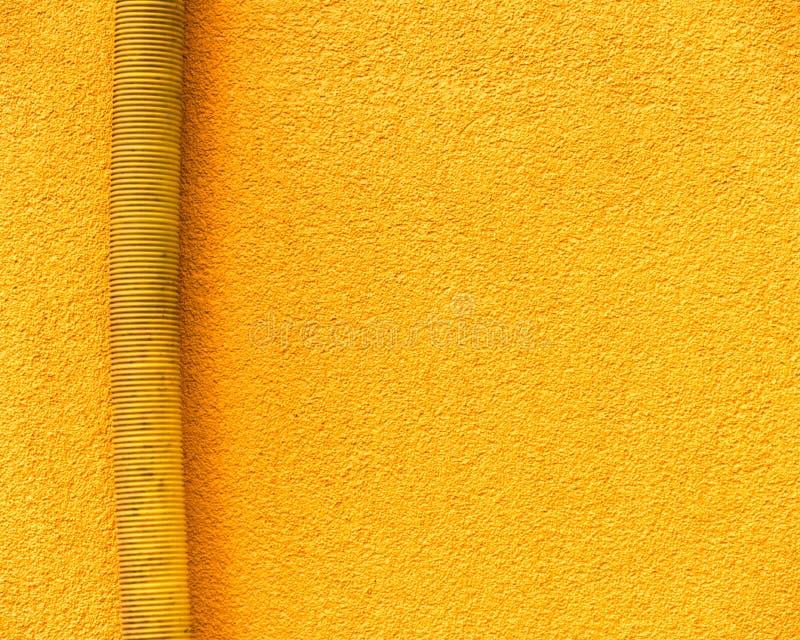 Желтая труба дождя на новом желтом фасаде стоковые изображения