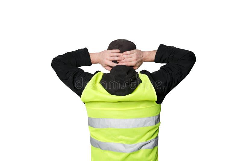 Желтые протесты жилетов Молодой человек стоит с его задней частью и держит его руки на его голове на изолированный стоковые изображения
