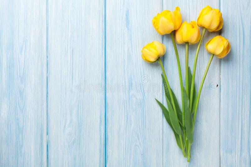 Желтые тюльпаны на деревянном столе стоковые фотографии rf