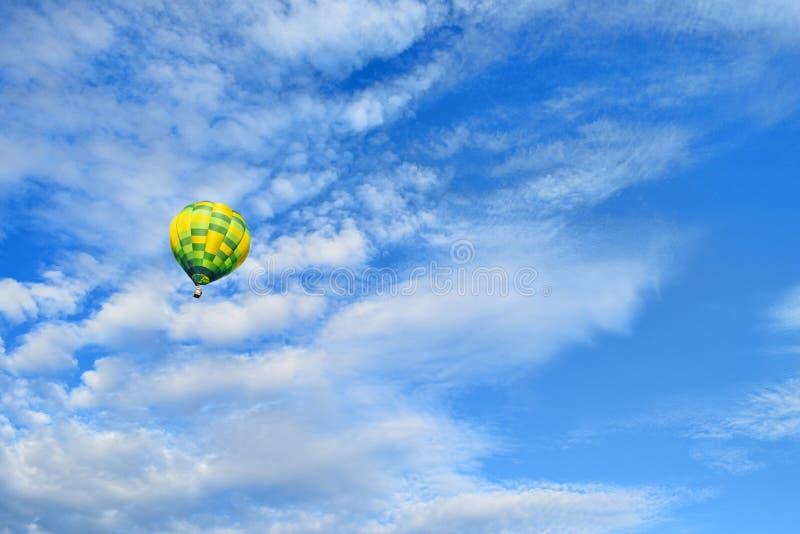 Желтый зеленый горячий воздушный шар поднимает до голубого неба с облаками стоковое изображение