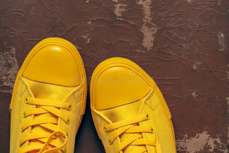 Желтый крупный план ботинок спортзала на старой затрапезной предпосылке стоковое изображение