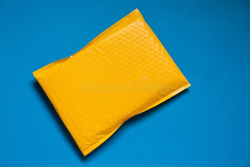 Желтый конверт сделанный обруча пузыря для предотвратить что-то от bumping или противоударного на голубой предпосылки стоковая фотография rf