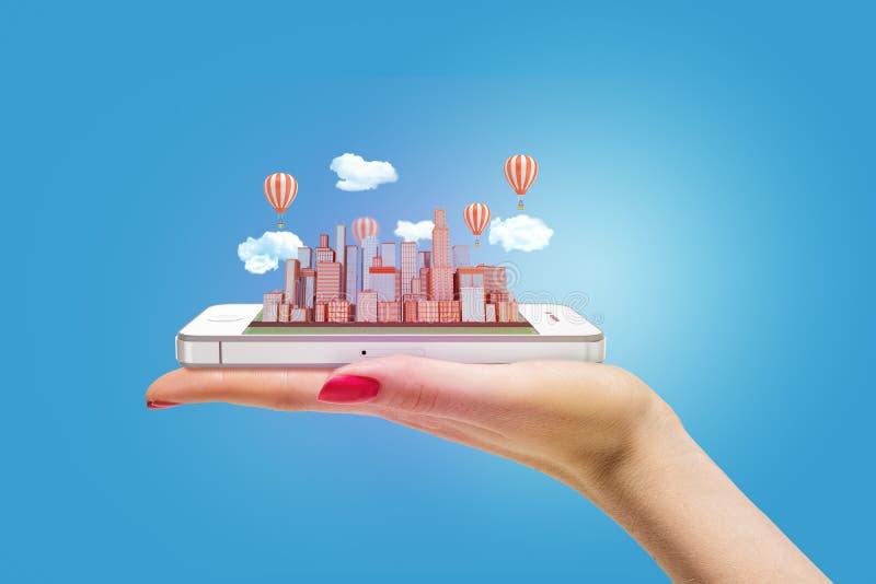 Женская рука держа модель города по умному телефону стоковые изображения