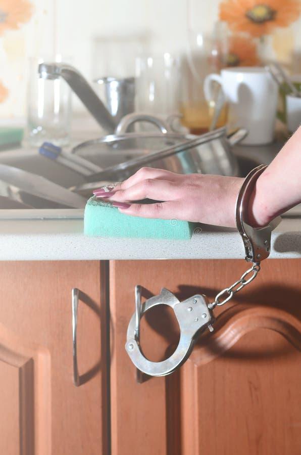 Женская рука с губкой, надеванной наручники к счетчику кухни с a стоковая фотография rf