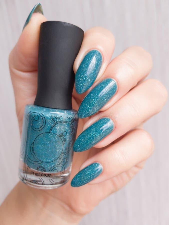Женская рука с темно-синими длинными ногтями и бутылкой стоковые фото