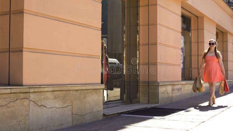 Женская shopaholic идя улица с сумками, защита интересов потребителя, приобретение подарков, продажа стоковое изображение rf