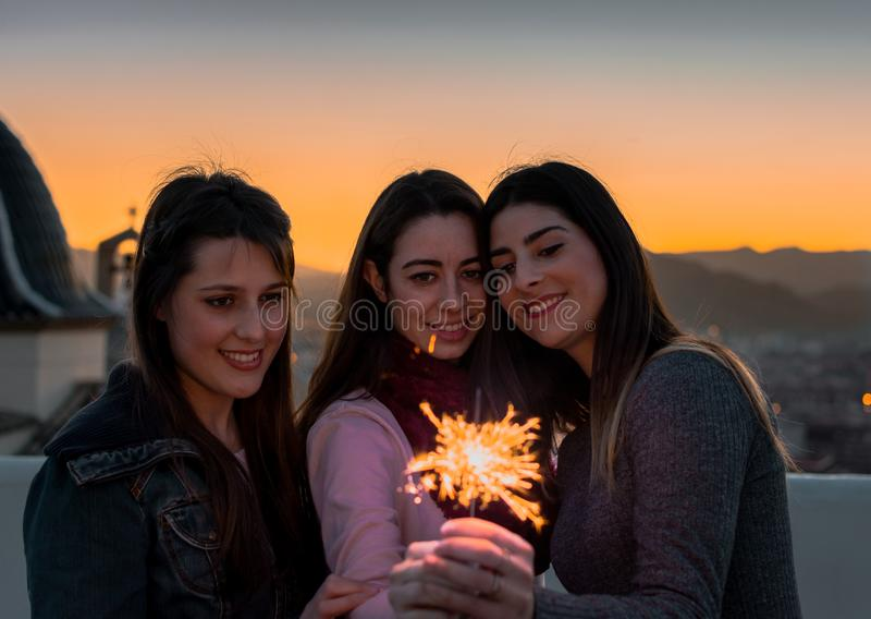 Женские друзья с бенгальскими огнями на открытом воздухе на заходе солнца стоковое изображение