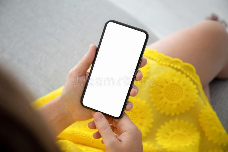 Женские руки в желтом телефоне удерживания платья с экраном стоковая фотография