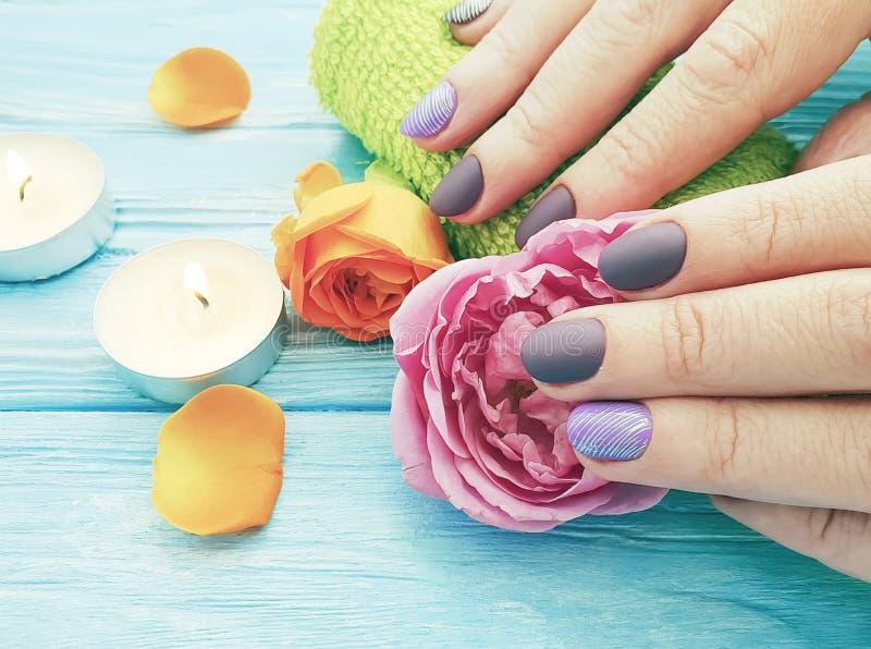 Женские руки, маникюр, цветок концепции подняли, свеча на деревянной предпосылке стоковое фото