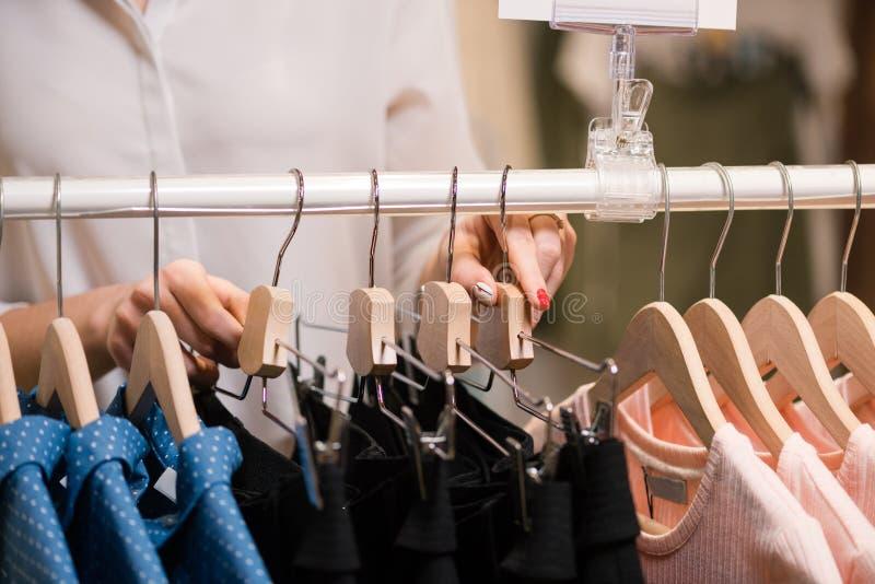 Женские руки положили одежды на стойку с вешалками стоковая фотография rf