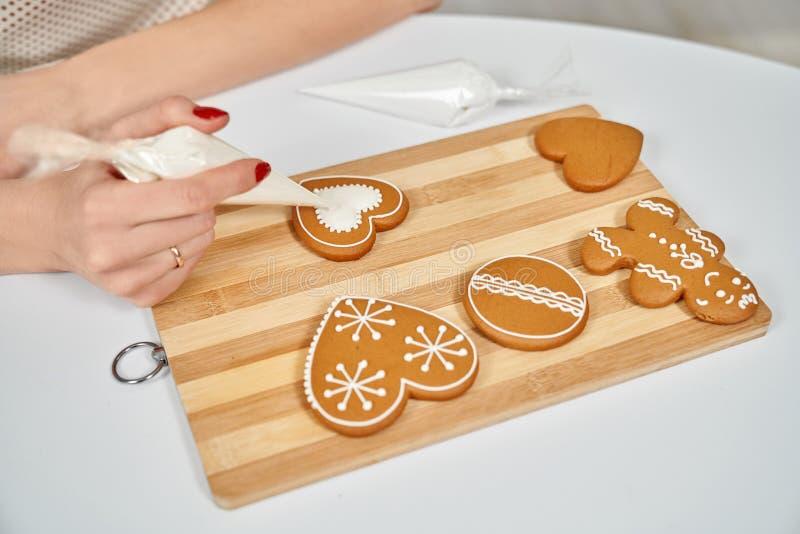 Женские руки украшая печенья имбиря с поливой сахара стоковое фото rf