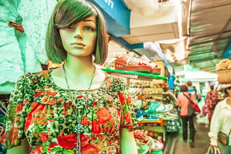 Женский манекен одетый в случайных одеждах во внешней витрине магазина, туристах и уличном торговце идя запачканные предпосылки P стоковая фотография rf