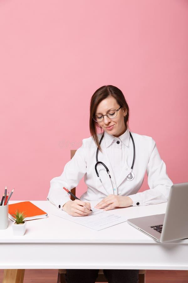 Женский доктор распологая на деятельность стола заполняя вне медицинские документы в больнице изолированной на пастельной розовой стоковые изображения