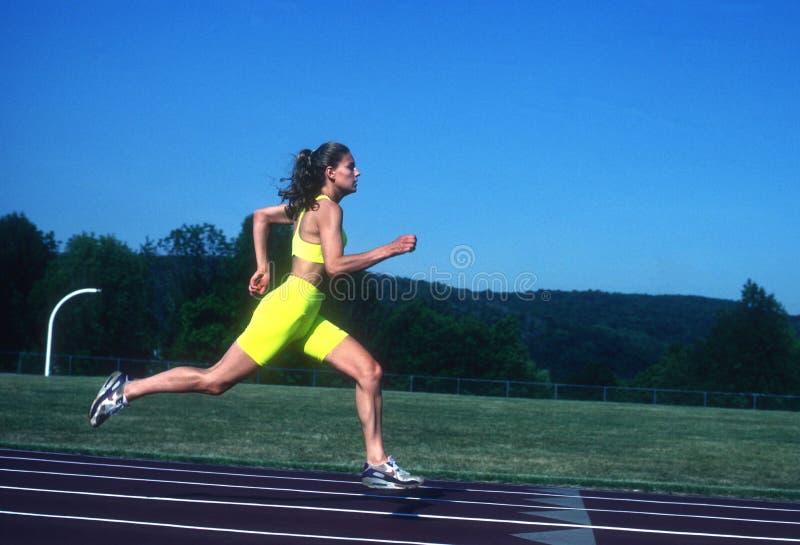 Женский спринтер бегуна работая и тренируя стоковые изображения
