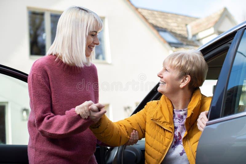Женский сосед давая старшей женщине подъем в автомобиль стоковые фотографии rf