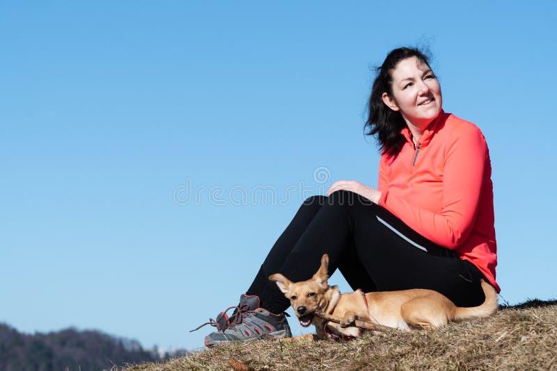 Женский hiker сидя на траве с собакой на наклоне холма и рассматривая плечо стоковые фотографии rf