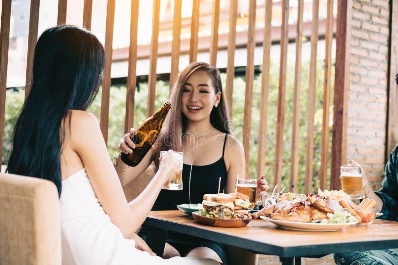 Женское лить пиво в стекле и питье совместно стоковая фотография