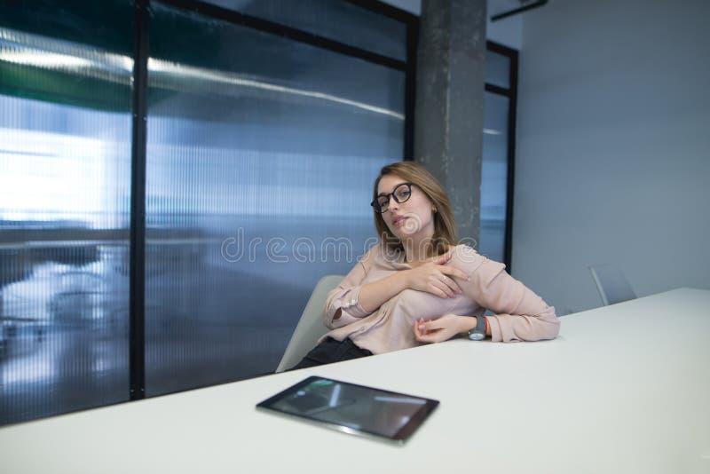 Женщина в стеклах представляет на рабочем месте в офисе около таблицы лежа на таблице стоковые фотографии rf