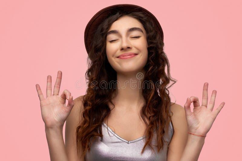 Женщина жизнерадостного брюнета молодая с радостным выражением, показывает знак ок с обеими одетыми руками, в случайной белой руб стоковое фото