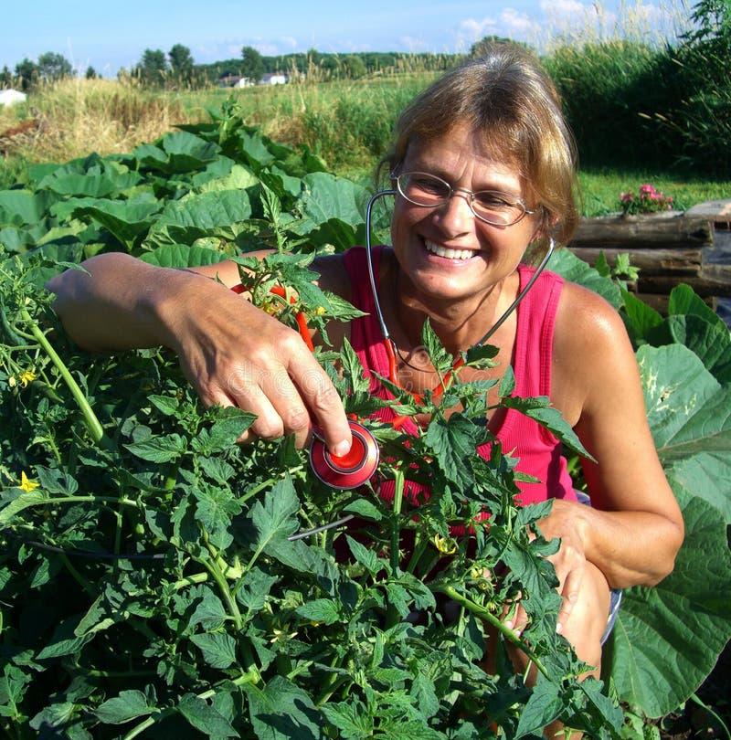 Женщина играя доктора в ее саде стоковое фото