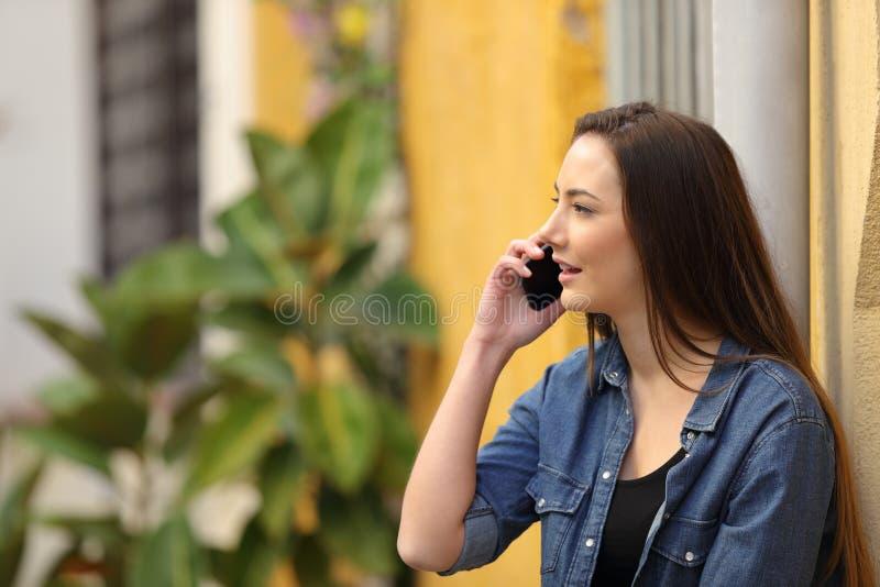 Женщина имея телефонный звонок стоя в улице стоковые фото