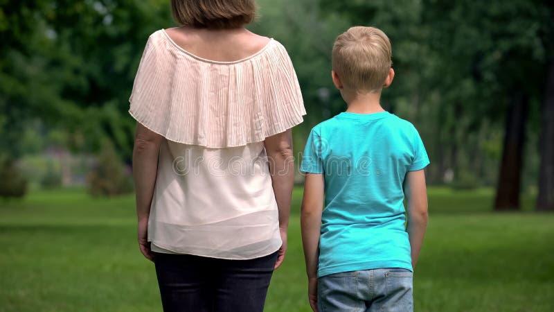 Женщина и мальчик держа руки, идя прочь совместно, концепция социальной защиты стоковые изображения rf