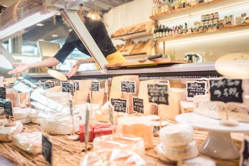 Женщина клерка магазина сортируя сыр в дисплее супермаркета стоковое изображение