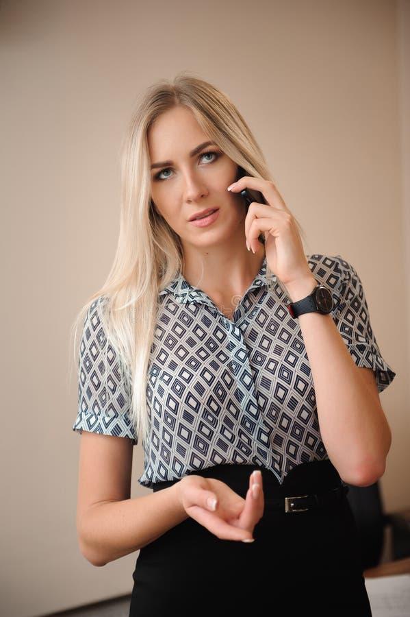 женщина красивейшего мобильного телефона дела говоря Молодая женская модельная работа с продажами в ярком офисе стоковые фото