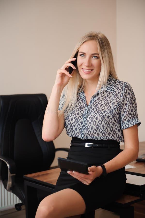 женщина красивейшего мобильного телефона дела говоря Молодая женская модельная работа с продажами в ярком офисе стоковая фотография