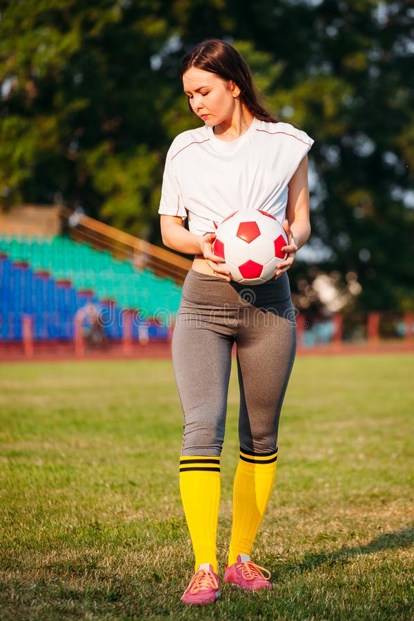 Женщина на футбольном поле с шариком в руке на предпосылке стоек стоковое изображение