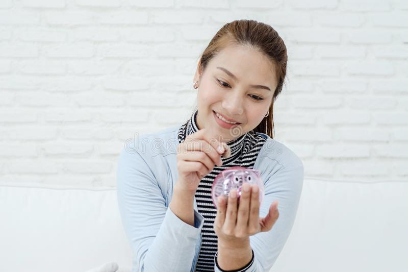Женщина несла голубую рубашку, усмехаясь и падая монетки в опарник стоковое изображение rf