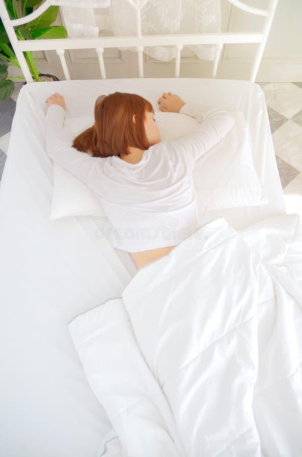 Женщина нося белое платье, она спит стоковая фотография