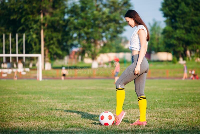 Женщина пиная футбольный мяч стоковая фотография rf