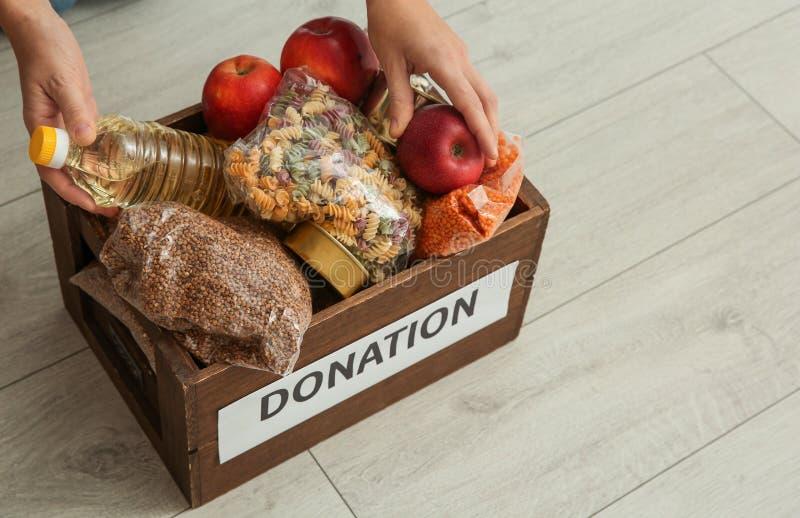 Женщина принимая еду от коробки пожертвования на деревянном поле стоковое фото rf