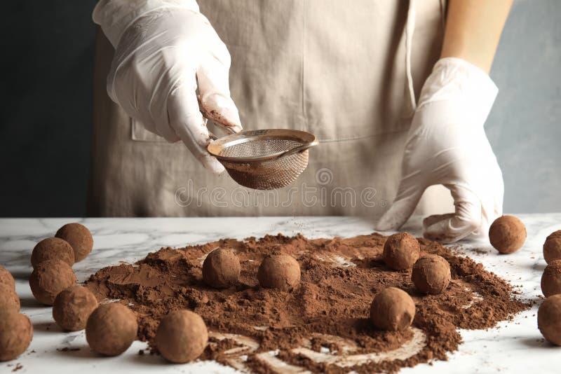 Женщина подготавливая вкусные трюфеля шоколада на таблице стоковая фотография rf