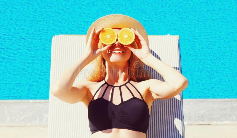 Женщина портрета держа в ее кусках рук апельсина пряча ее глаза на предпосылке бассейна открытого моря стоковые изображения rf