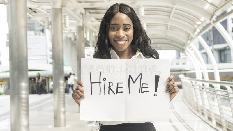 Женщина дела портрета африканская держит бумажную доску со словом для того чтобы нанять меня на пешеходном на открытом воздухе го стоковое фото