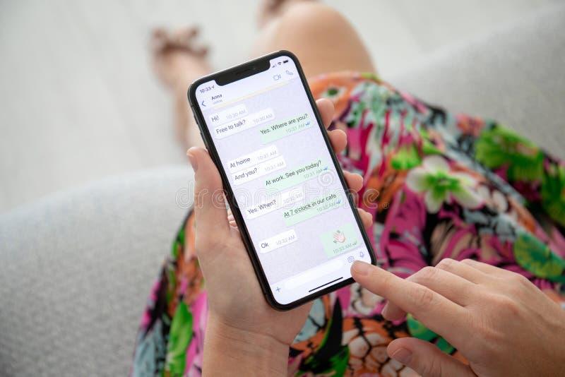 Женщина держа iPhone x с социальным обслуживанием WhatsApp сети стоковое фото