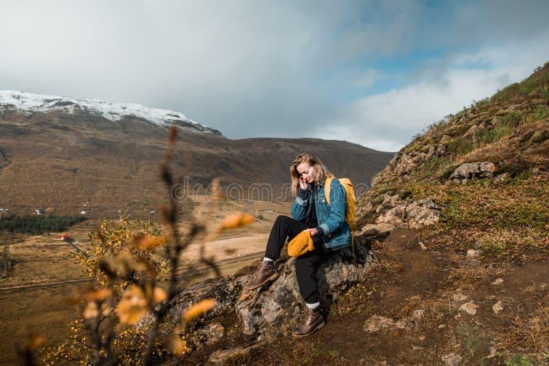 Женщина сидя на скалистой скале и смотря изумляющ нордический ландшафт, Исландию Перемещение и природа стоковое фото