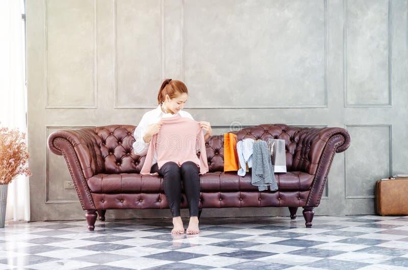 Женщина сидя на софе она держит розовую рубашку и усмехается стоковое фото rf