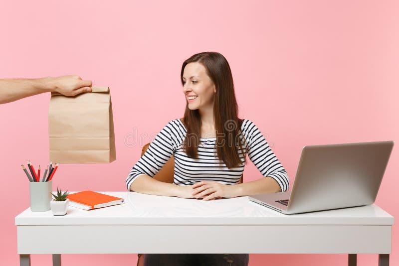 Женщина смотря на коричневом ясном пустом пустом бумажном мешке ремесла, работе на столе с ноутбуком ПК изолированным на розовой  стоковое фото