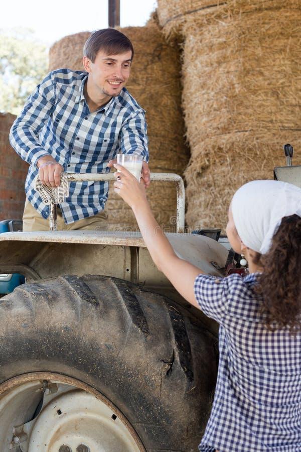 Женщина страны дает к стеклу водителя трактора человека молока на ферме стоковое фото rf
