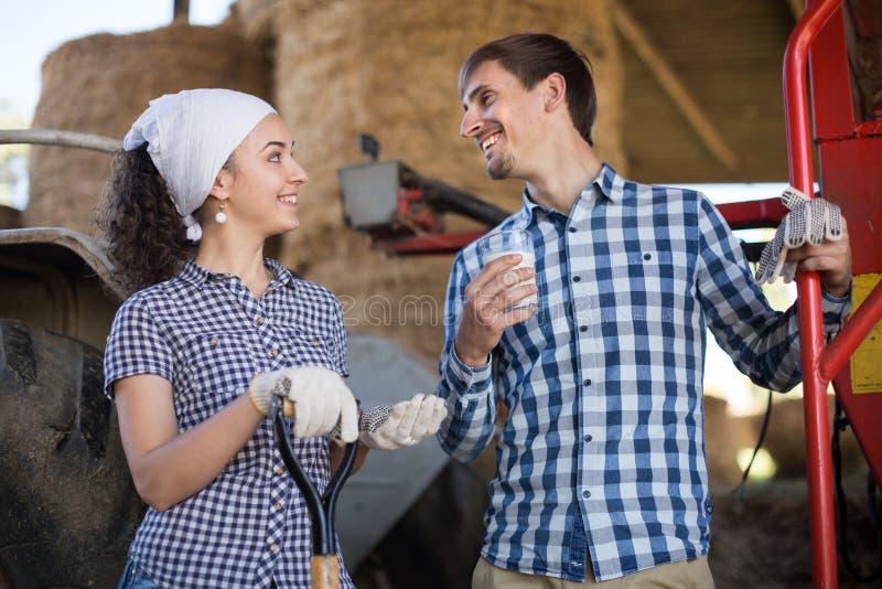 Женщина страны дает к стеклу водителя трактора человека молока на ферме стоковая фотография rf