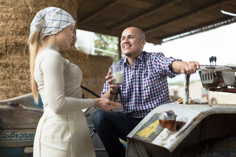 Женщина страны дает к стеклу водителя трактора человека молока на ферме стоковые изображения rf