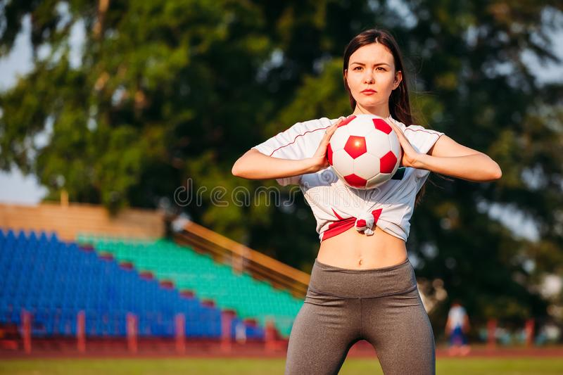 Женщина с футбольным мячом в ее руках на футбольном поле на предпосылке стоек стоковое фото