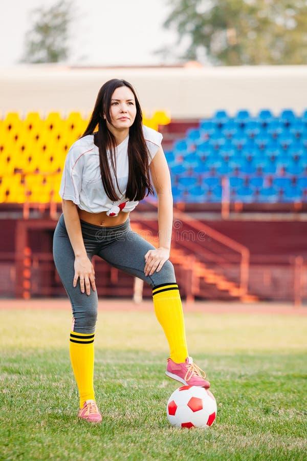 Женщина с футбольным мячом на футбольном поле стоковая фотография rf