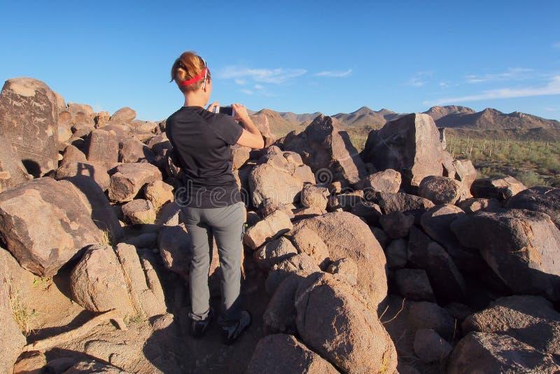 Женщина фотографируя петроглифы в национальном парке Saguaro стоковое изображение