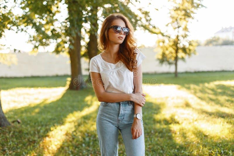Женщина хипстера красивого redhead молодая в винтажных голубых джинсах в белой футболке в ультрамодных солнечных очках стоит в па стоковая фотография